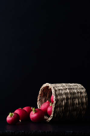 Side view of a small basket of radishes, tipped over and spilling on to slate surface with black background.