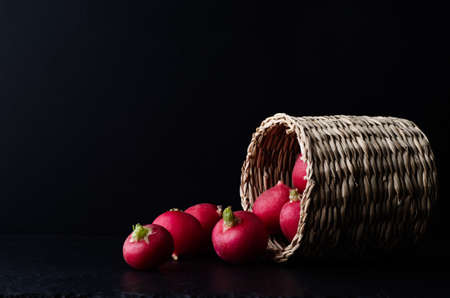 Basket filled with radishes on its side and spilling out on to slate surface with black background. Zdjęcie Seryjne