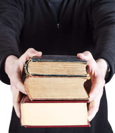 A pile of three old text books, handed forward to viewer by man in dark casual clothing.
