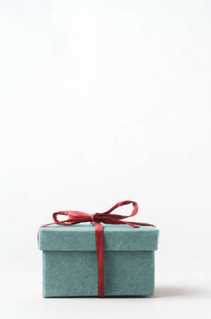 A simple, plain, turquoise gift box with lid. Closed and tied with red raffia ribbon. Copy space above.
