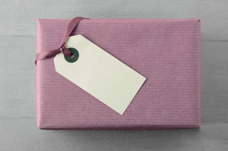 Overhead view of a gift box, wrapped in plain mauve paper with ribbon and blank gift tag on grey wood table background. Zdjęcie Seryjne