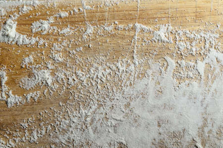 Overhead shot of an old, scratched wooden chopping board, dusted with a sprinkling of white flour. Zdjęcie Seryjne