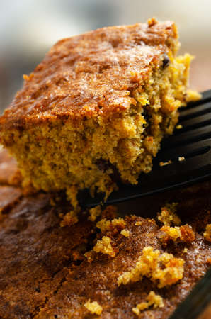 A slice of carrot cake, lifted out of baking dish with remainder and crumbs below. Close up side corner view.
