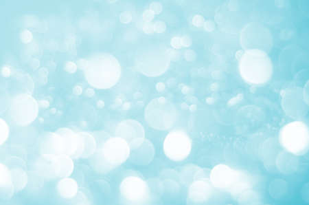A bokeh background of large and small white light circles softly blurred on a pale blue background.