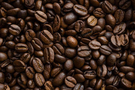 Darkly lit roasted coffee beans, piled together and filling frame to create a background texture in multiple shades of brown and gold. Foto de archivo