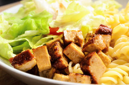 Close up of cooked tofu pieces with pasta and salad in a white bowl on light wood table. Vegetarian and vegan meal.