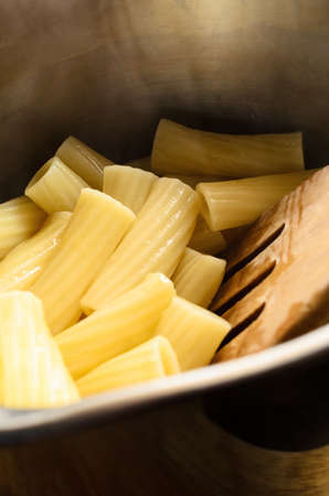 Freshly cooked and drained hot pasta (Rigatoni) in stainless steel saucepan with wooden spatula. Zdjęcie Seryjne