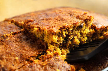 A crumbly square slice of freshly baked carrot cake being lifted from baking dish for serving. Close up just above eye level. Zdjęcie Seryjne