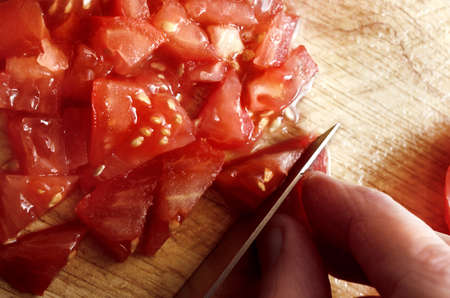 Overhead shot of hand holding knife to chop and slice juicy, red raw salad tomatoes on wooden chopping board.