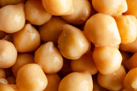 Close up of chickpeas (garbanzo beans), drained and wet, filling frame as food background.