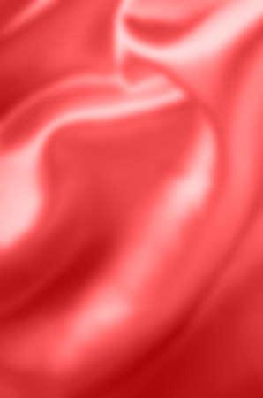 Coral satin fabric, draping with soft folds. Blurred background. Zdjęcie Seryjne