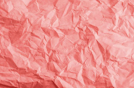 Crumpled, creased and unfolded paper background texture in a coral hue. Zdjęcie Seryjne