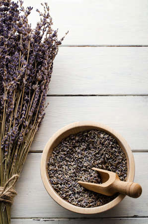 Overhead view of a tied lavender flower bunch next to a bowl of dried buds with wooden scoop on white planked table.