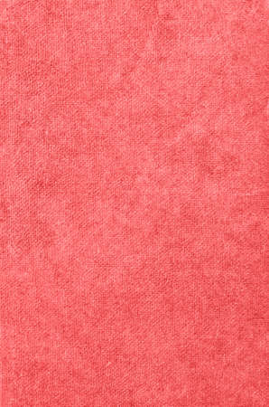 Background texture of old fabric book cover in warm pink coral hue.