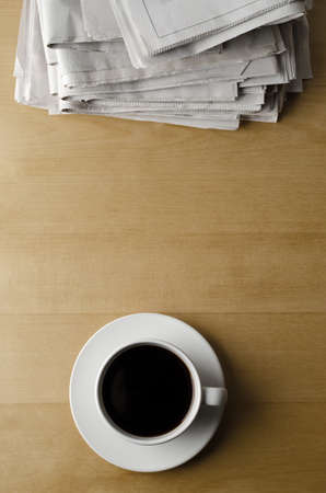 Overhead shot of a cup and saucer of black coffee placed on a light wood laminate table with a pile of newspapers. Фото со стока
