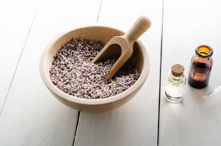 Wooden bowl full of dried lavender flower buds with scoop, next to  glass vials filled with oils on white painted wood plank table..  Zdjęcie Seryjne