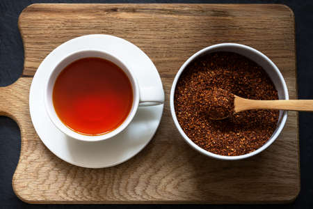 Overhead shot of a cup and saucer containing rooibos (redbush) tea with white bowl of leaves scooped in a wooden spoon. Wooden board with black slate below.