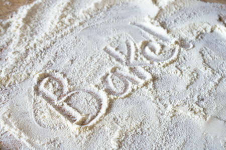 The word 'Bake!' written into messily scattered flour revealing wooden board below.