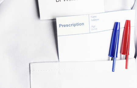 A blank prescription  and two pens poking out from a Doctor's white coat pocket, providing copy space for a message.