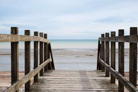 Shot taken from point of view of standing on a wooden bridge, looking out towards the horizon at the beach at low tide.