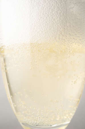 Close up (macro) eye level shot of a fluted glass freshly filled with champagne, topped with frothy white bubbles.