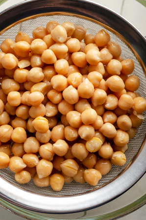 Overhead shot of chickpeas (garbanzo beans) draining through a steel sieve into a glass bowl on white painted wood planked table.