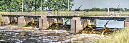 Barrage in and pedestrian bridge across the river Vecht near Zwolle, the Netherlands Stock Photo