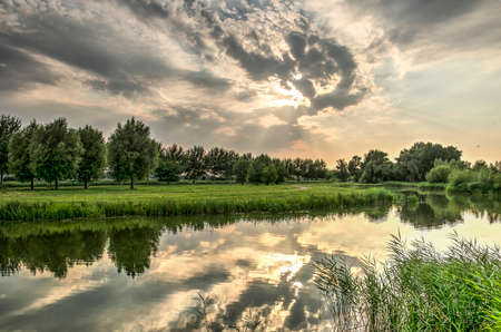Dramatic evening skies reflecting in the calm water of Koedood river on the island of IJsselmonde, just south of Rotterdam. Stock fotó