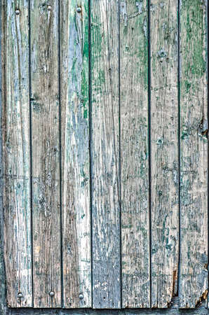 Part of a wooden door with vertical planks and peeling paint in shades of green, blue, white and brown Фото со стока