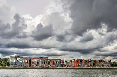 View across the Merwede river towards the waterfront of the town of Papendrecht, with modern appartment buildings under a stormy sky
