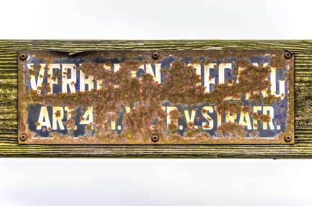 Viejo cartel de entrada prohibida holandés, sus palabras casi ilegibles a través del óxido y la suciedad, sobre una superficie de madera