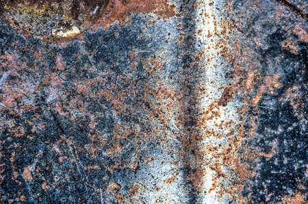 Rough dark steel surface with patches of rust and white paint and other irregularities