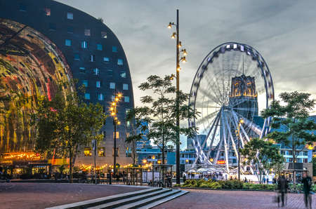 Rotterdam, The Netherlands, September 15, 2018: Binnenrotte square at dusk with the Markthal, Ferris wheel The Dinner Wheel and Saint Lawrence Church
