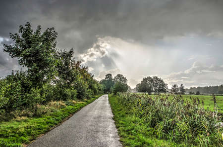 Narrow asphalt road between meadows and low forests near Ankeveen, The Netherlands with some raindrops falling from a diverse and rapidly changing sky