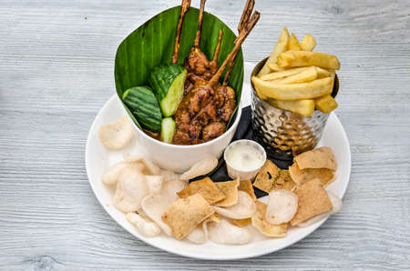 Indonesian inspired dutch dinner with chicken sateh, french fries, prawn crackers and mayonaise on a white wooden table