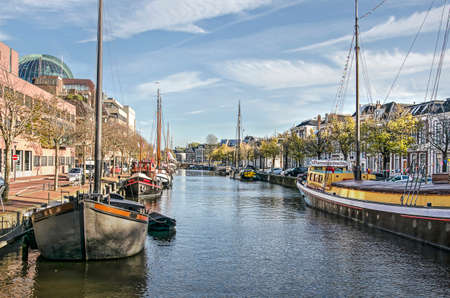 Leeuwarden, The Netherlands, November 3, 2018: historic barges in Zuiderstadsgracht canal, with old houses on the right and more modern buildings on the left