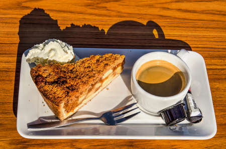 Sun shining on and casting shadows of a square white plate with a cup of black coffee and a piece of apple pie with whipped cream