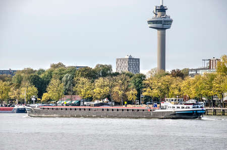 Rotterdam, The Netherlands, November 6, 2018: view of the Nieuwe Maas river with a passing inland barge and The Park and the Euromast observation tower in the background