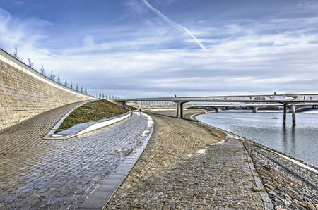 A fascinating composition of slopes, ramps, stairs and walls as well as two bridges at the bank of the new channel of the river Waal near Nijmegen, The Netherlands, on a sunny day in winter