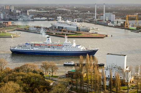 Rotterdam, The Netherlands, December 10, 2018: cruiseship Marco Polo passes Park Quay on its way to the sea, with former cruiseship SS Rotterdam, now a hotel, in the background