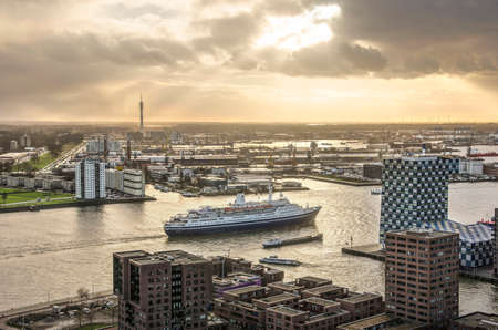 Rotterdam, The Netherlands, December 10, 2018: a dramatic sky over the river Nieuwe Maas, the adjacent harbour and residential areas and cruiseship Marco Polo