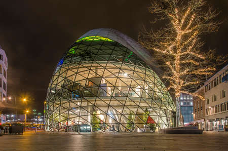 Eindhoven, The Netherlands, December 14, 2018: Glass dome-shaped clothing store and tree with Christmas decorations on Emmasingel at night