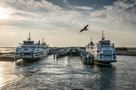 Texel, The Netherlands, July 21, 2018: two ferry boats docked in the harbour as seen from a third boat leaving the island whilst a seagull is flying by Editorial