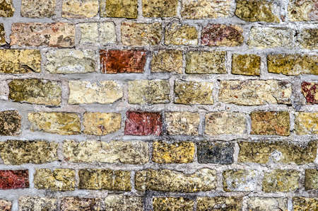 Close-up of an old brick wall with relatively large blocks in various shades of red, yellow and brown, held together with grey mortar 版權商用圖片