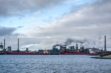 IJmuiden, The Netherlands, December 22, 2018: view across Northsea Canal towards the Tata steelworks under a dramatic sky Editoriali