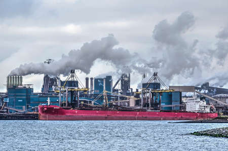 IJmuiden, The Netherlands, December 22, 2018: smoking chimneys and a red bulk carrier moored at the Tata steelworks on the opposite side of the Northsea Canal