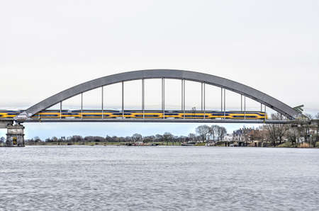 Culemborg, The Netherlands, March 4, 2017: Yellow Dutch Railways passenger train on the steel arch bridge across the river Lek Editorial