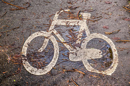 White shape of a bicycle on the wet asphalt of a bicycle lane, covered with fallen twigs