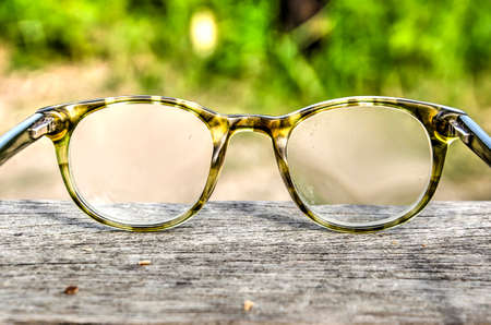 Reading glasses in a plastic frame on a rough wooden surface against a grain background Imagens