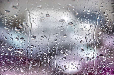 Raindrops creating a pattern on a glass window, with unrecognizable shapes behind it, on a rainy day in Iceland